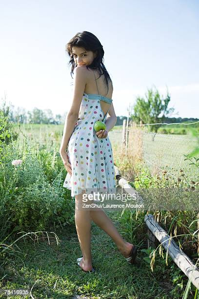 Young woman standing in garden, holding apple behind back, looking over shoulder at camera