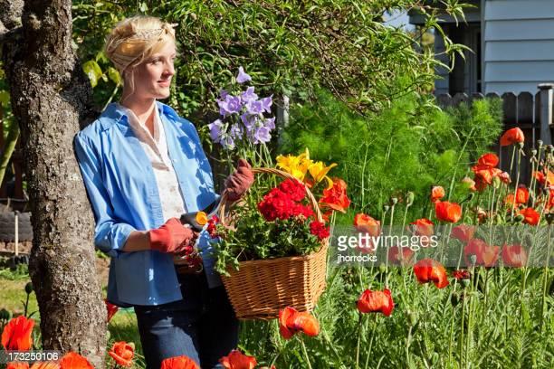Junge Frau im Garten mit Korb mit Blumen