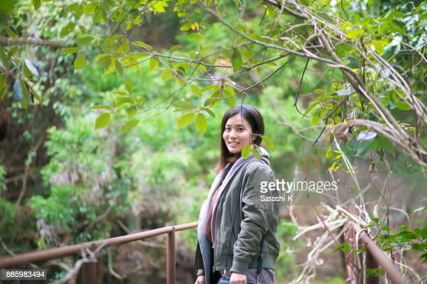 緑の森に立っている若い女性