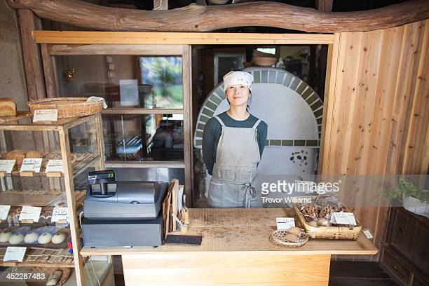 A young woman standing in her bakery