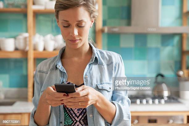 Young woman standing in kitchen with cell phone