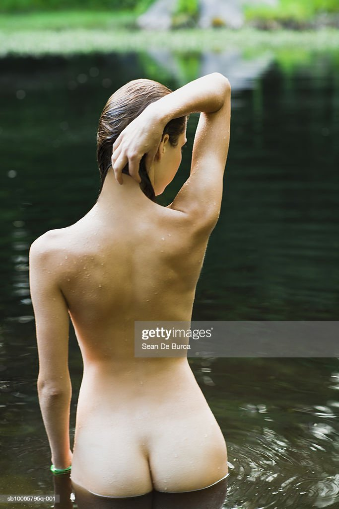 Young woman standing in lake water, rear view : Stock Photo