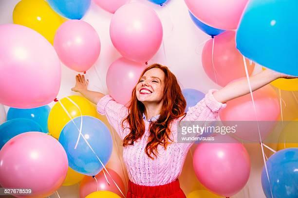 Mujer joven de pie en muchos globos
