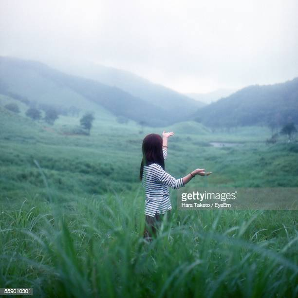 Young Woman Standing In Meadow With Raised Arms