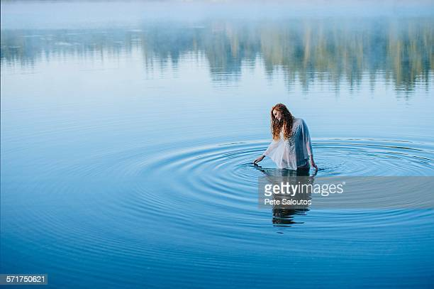 Young woman standing in middle of lake ripples looking down