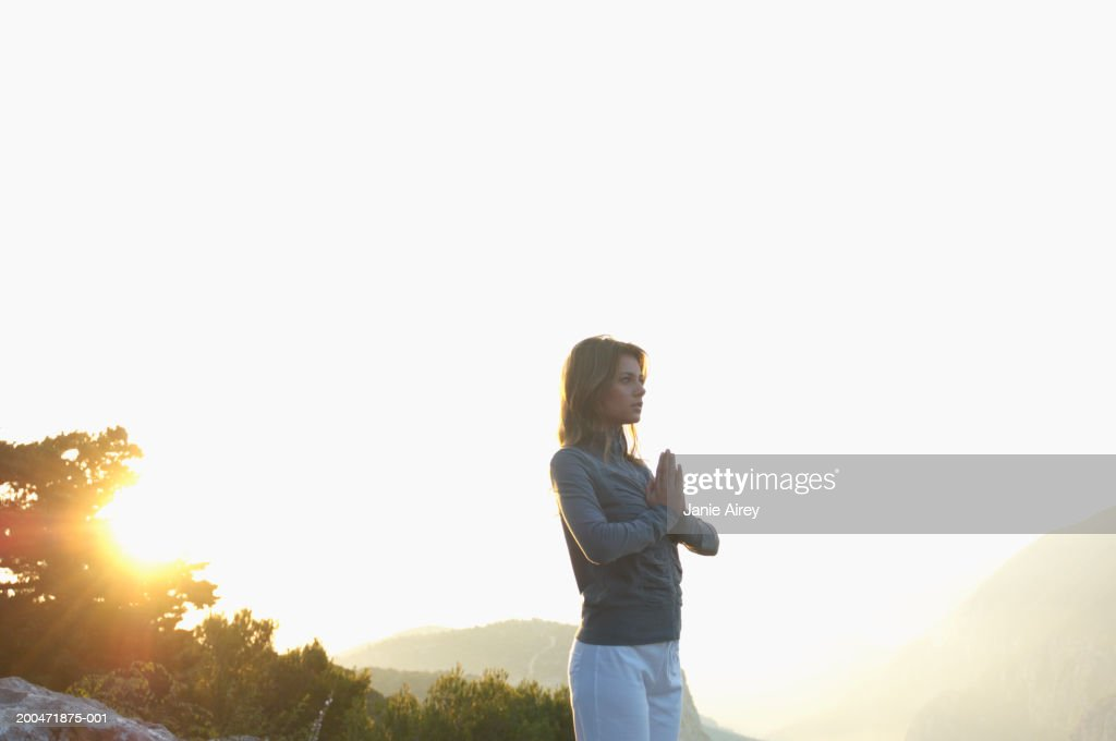 Young woman standing in mountain landscape, hands pressed together