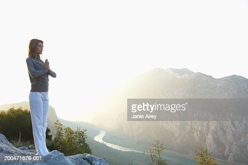 Young woman standing in mountain landscape, hands pressed together : Stock Photo