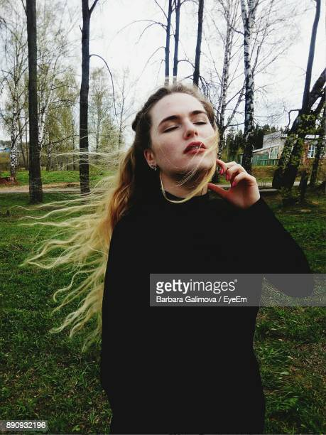 Young Woman Standing In Park Against Sky