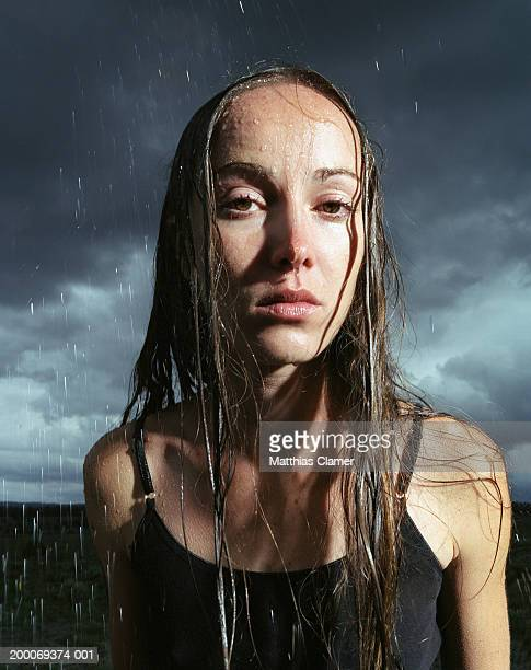 Young woman standing in rain, portrait