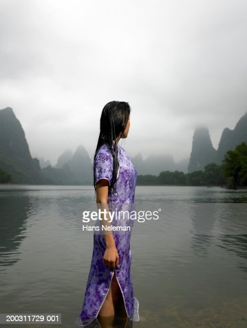Young woman standing in river, looking at pinnacles, side view : Stock Photo
