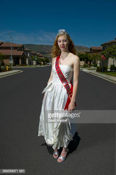 Young woman standing in road, wearing tiara and 'Southern Belle' sash