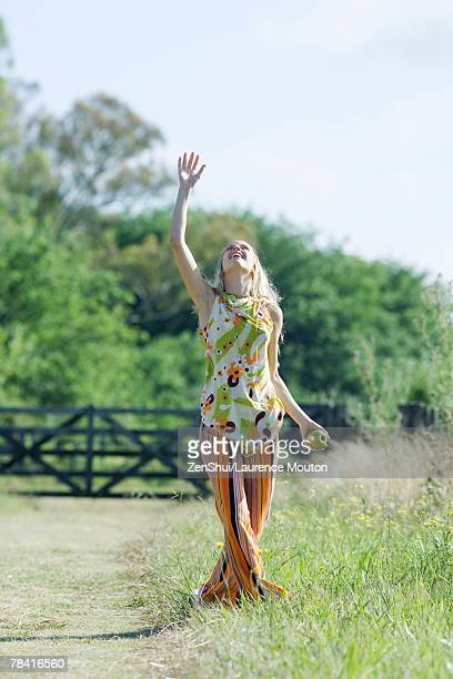 Young woman standing in rural field with arm raised, looking up, apple in hand