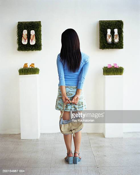 Young woman standing in shoe gallery, rear view