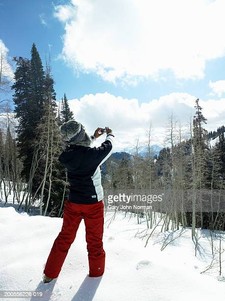 Young woman standing in snow taking photo, rear view