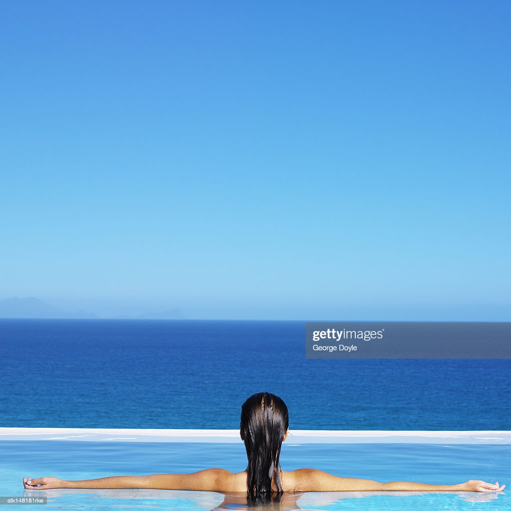 young woman standing in swimming pool splashing water rear view : Stock Photo