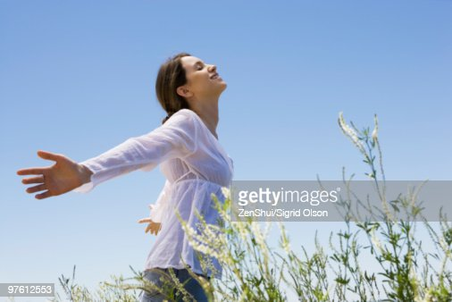Young woman standing in tall grass with arms out, eyes closed