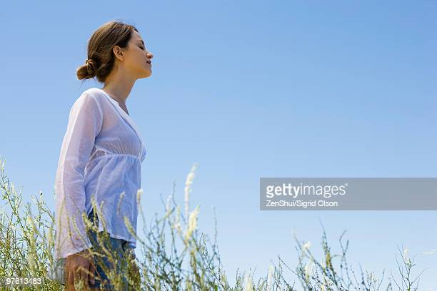 Young woman standing in tall grass with eyes closed, side view