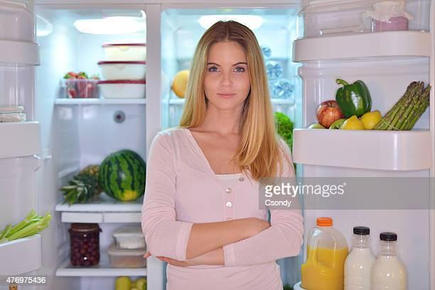 Young woman standing in the fridge door