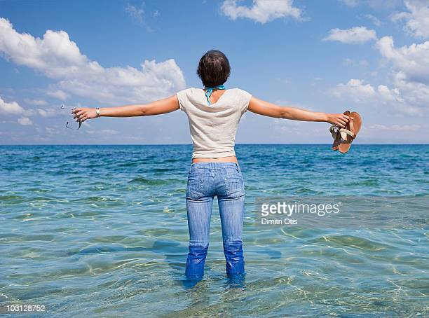 Young woman standing in the ocean wearing jeans