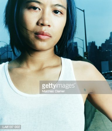 Young woman standing in urban street, portrait : Stock Photo