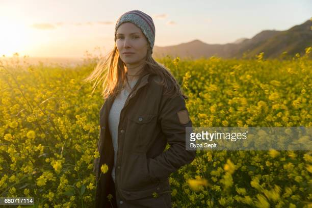 Young Woman Standing in Wildflowers at Sunset