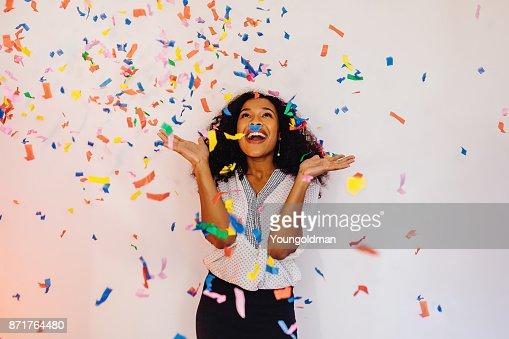 Mujer joven que está parado en el interior bajo colorido confeti : Foto de stock