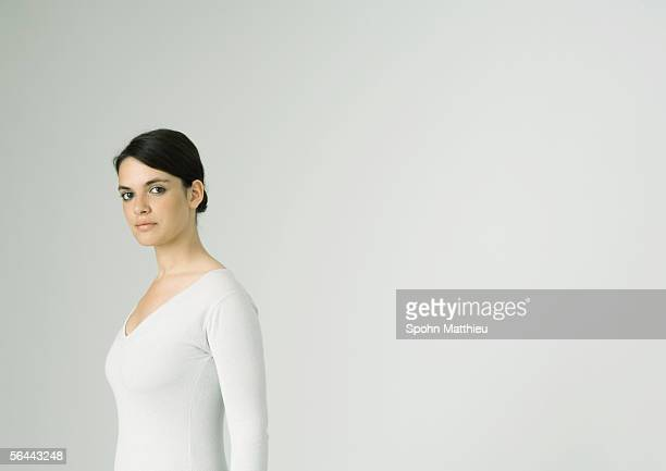 Young woman standing, looking at camera
