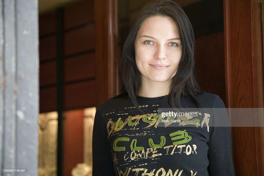 Young woman standing near door, smiling, portrait : Stock Photo