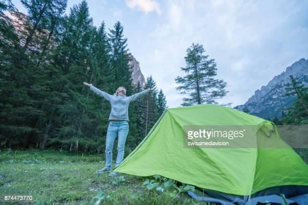 Ung kvinna som står nära tält armarna utsträckta