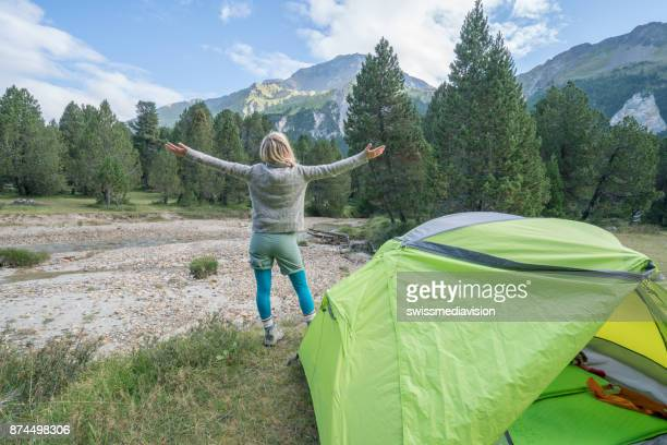 Young woman standing near tent arms outstretched, Switzerland