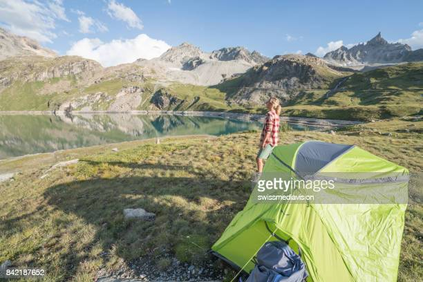 Young woman standing near tent contemplating the beauty in nature