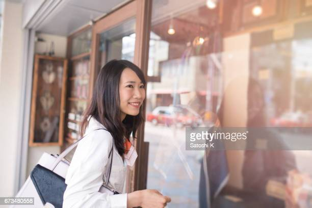 Young woman standing nearby retail store
