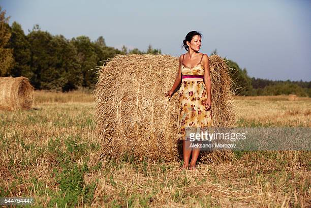 Young woman standing next to a stack of hay