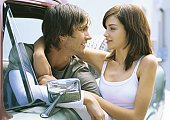 Young woman standing next to pick-up truck with arm around boyfriend in driver's seat