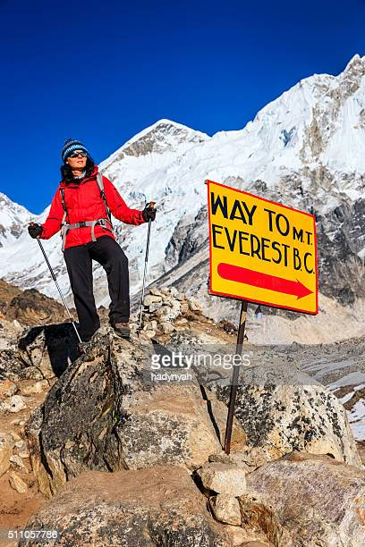 Young woman standing next to signpost 'Way to MountEverest BaseCamp'