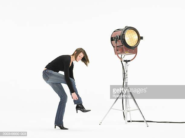 Young woman standing next to spotlight, adjusting boot