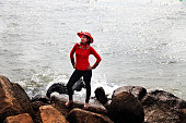 Young woman standing on the rock near the seashore and also enjoying fresh air.