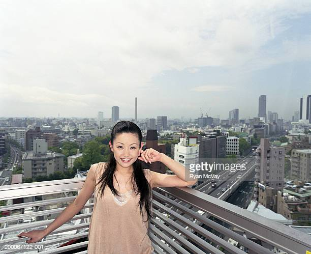 Young woman standing on balcony, cityscape in background, portrait