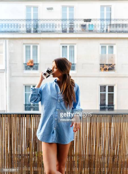 Young woman standing on balcony drinking coffee