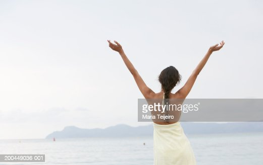 Young woman standing on beach, arms raised, rear view