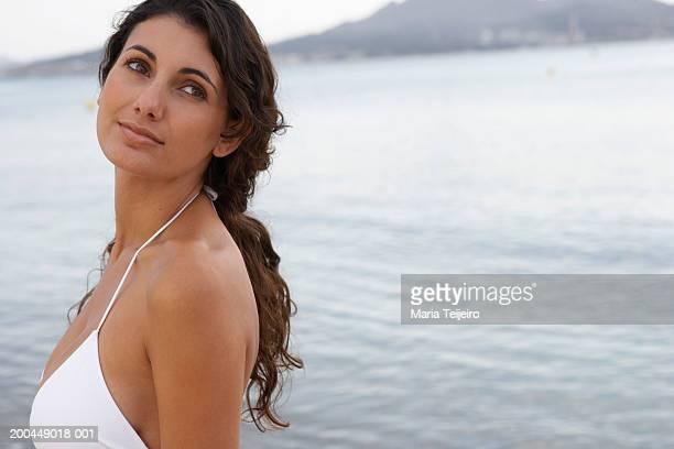 Jeune femme debout sur la plage, Regarder par-dessus l'épaule