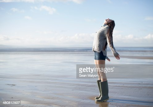 Young woman standing on beach looking up, Brean Sands, Somerset, England