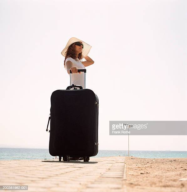 Young woman standing on beach with suitcase, low angle view