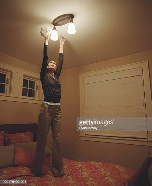 Young woman standing on bed to dust light fixture