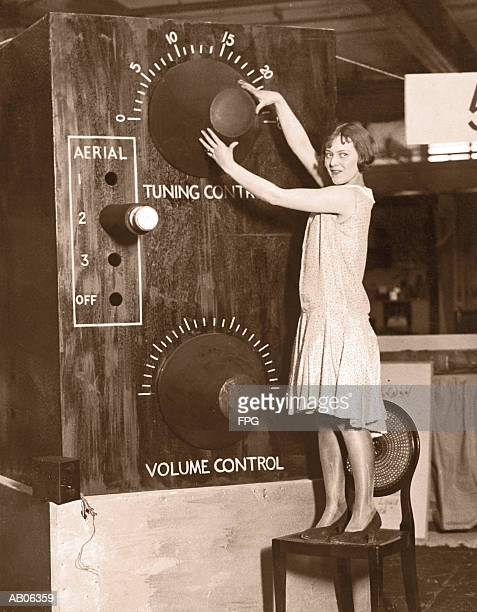 Young woman, standing on chair, adjusting giant radio tuner (B&W)