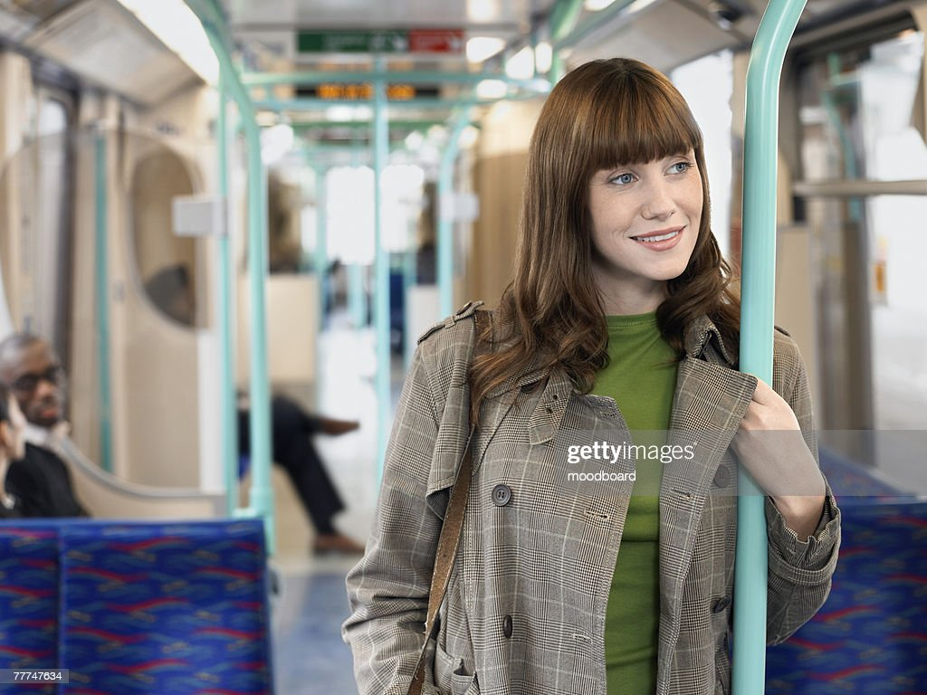 Young Woman Standing on Commuter Train : Stock Photo