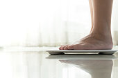 young woman standing on digital weight scale