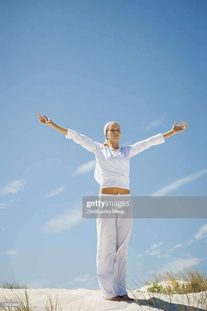 Young woman standing on dune, meditating