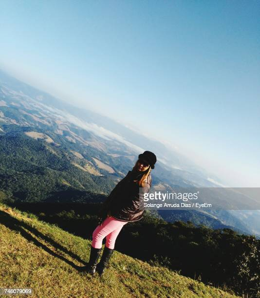 Young Woman Standing On Green Mountain