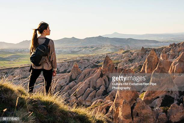 Young woman standing on hill, looking at view, Goreme National Park, Goreme, Cappadocia, Anatolia, Turkey